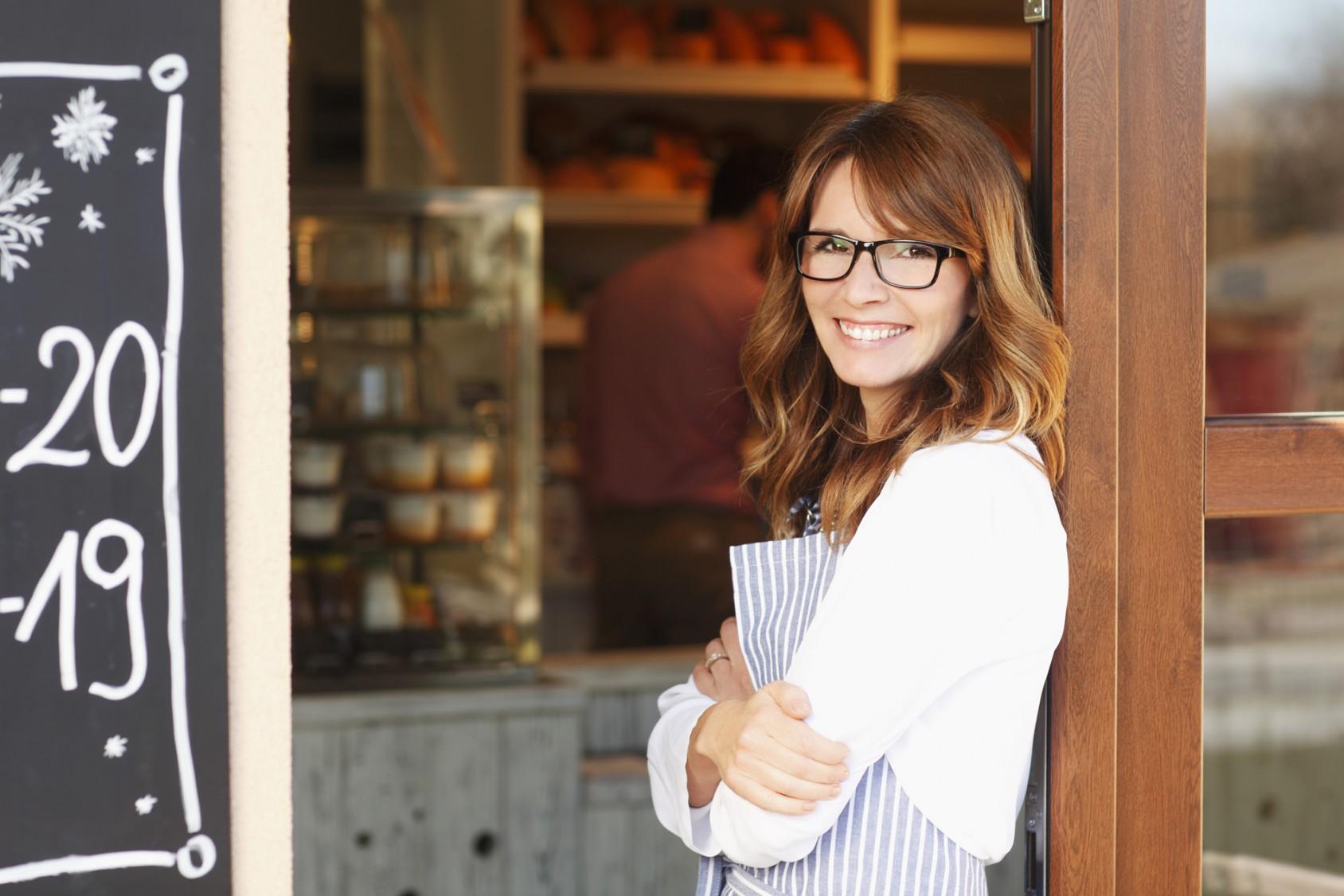 junge frau steht vor ihrem start up restaurant